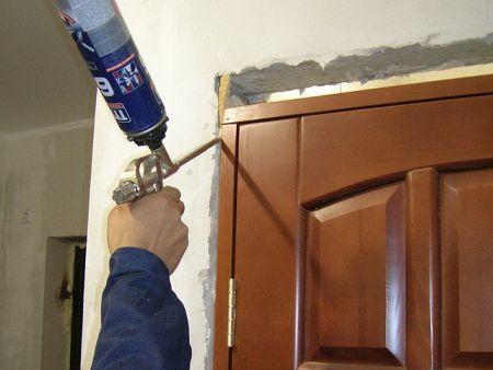 Запенивание дверного проёма во время установки